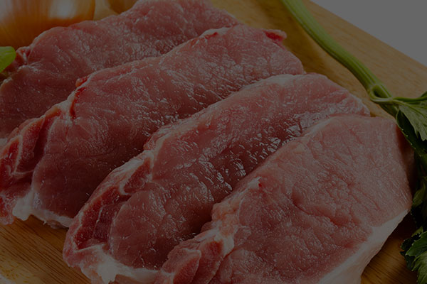 Background image of a row of boneless pork chops on a cutting board